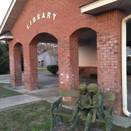 Graceville Branch entrance arches and children reading on a bench statue.